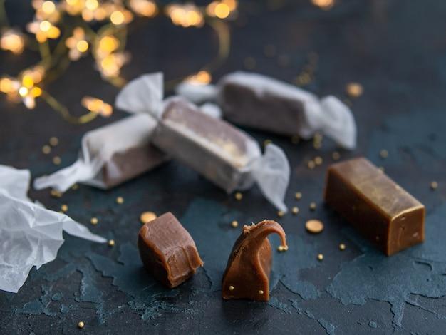 Doces de caramelo de ouro caramelo fresco em papel branco sobre fundo azul escuro com festão em forma de estrelas luminosas.