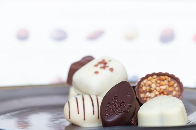Doces de chocolate assorted do gourmet em formas e em cores diferentes no prato.
