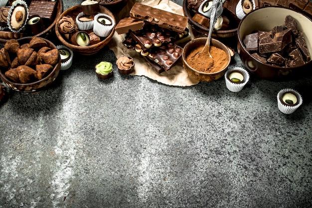 Doces de chocolate com cacau em pó. sobre um fundo rústico.