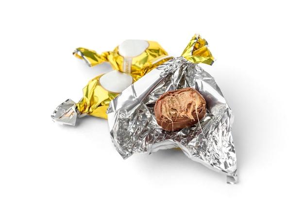 Doces de chocolate com praliné em invólucro dourado, isolado no fundo branco.