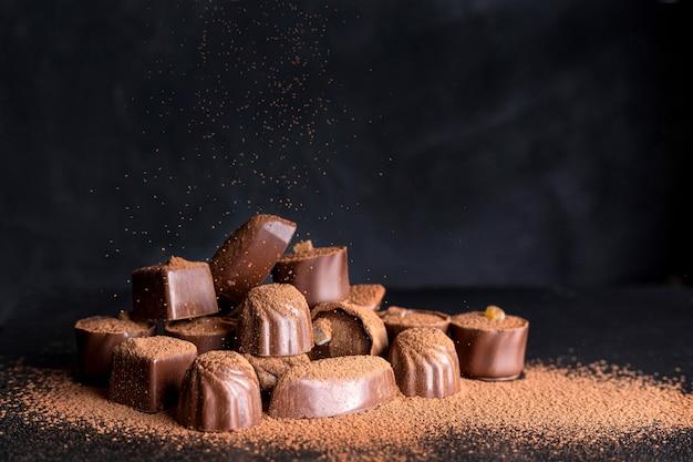 Doces de chocolate de alto ângulo com cacau em pó
