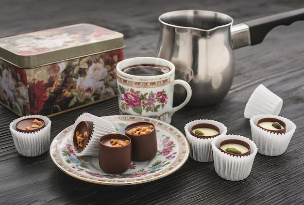 Doces de chocolate e acessórios para café em uma mesa escura