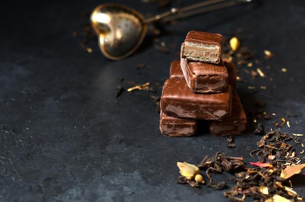 Doces de chocolate e chá preto com ervas. coador de chá de metal.