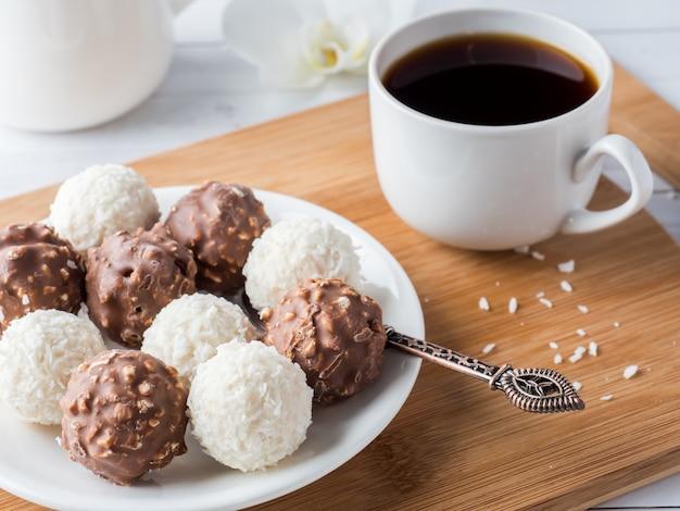 Doces de chocolate e coco em uma tigela em uma bandeja de madeira orquídea de xícara de café