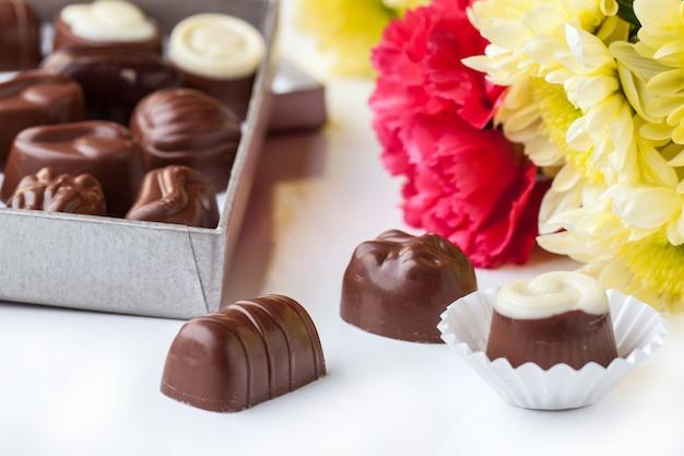 Doces de chocolate e flores sobre branco