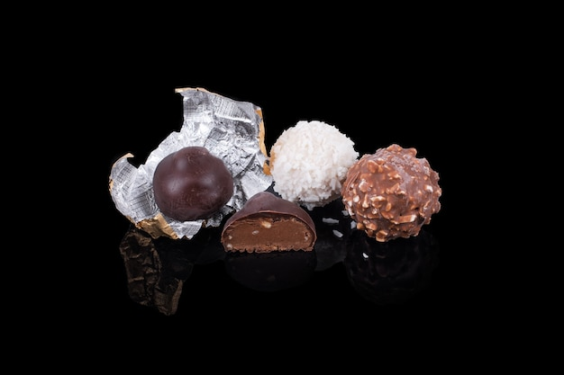 Doces de chocolate em cores e formas diferentes de superfície reflexiva preta