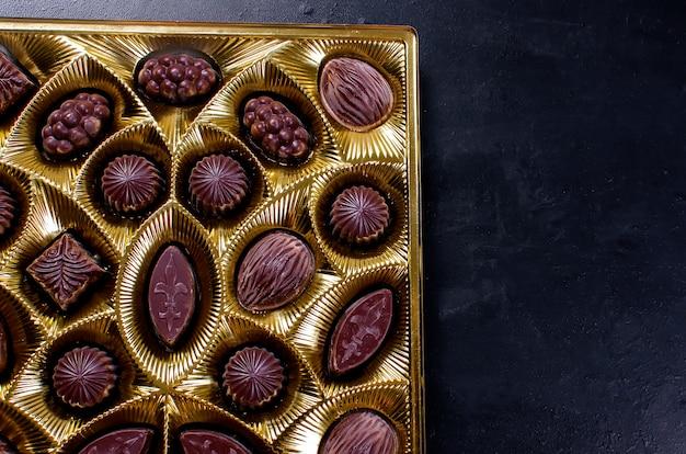 Doces de chocolate em uma caixa em um escuro
