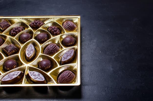 Doces de chocolate em uma caixa em um fundo escuro