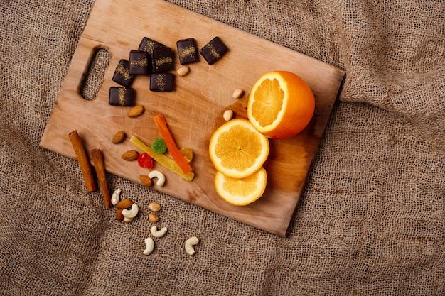 Doces de chocolate laranja canela e nozes na mesa de madeira.