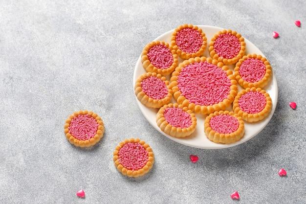 Doces de cor rosa, balas, merengue e açúcar.