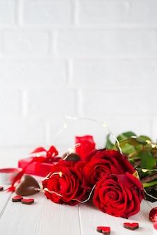 Doces de corações de chocolate e rosa vermelha em fundo branco de madeira