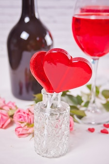 Doces de forma de coração vermelho com copos de vinho de uva vermelho com garrafa e rosas no fundo