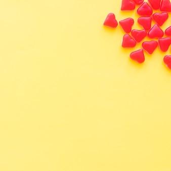 Doces de forma de coração vermelho no canto do pano de fundo amarelo