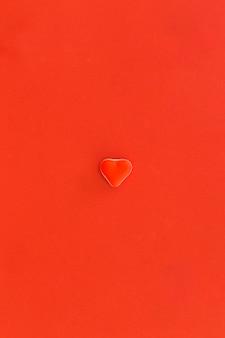 Doces de forma de coração vermelho no centro do fundo vermelho