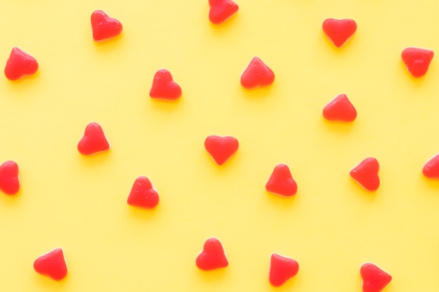 Doces de forma de coração vermelho sobre fundo amarelo