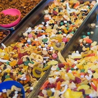 Doces de frutas coloridas no recipiente para venda
