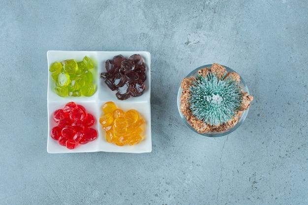 Doces de gelatina coloridos com uma árvore de natal em mármore.