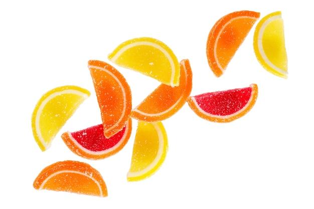 Doces de gelatina de açúcar em forma de fatias de frutas isoladas em um fundo branco