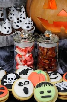 Doces de gelatina em forma de mandíbulas e minhocas em uma jarra sobre uma mesa de halloween, entre outros doces