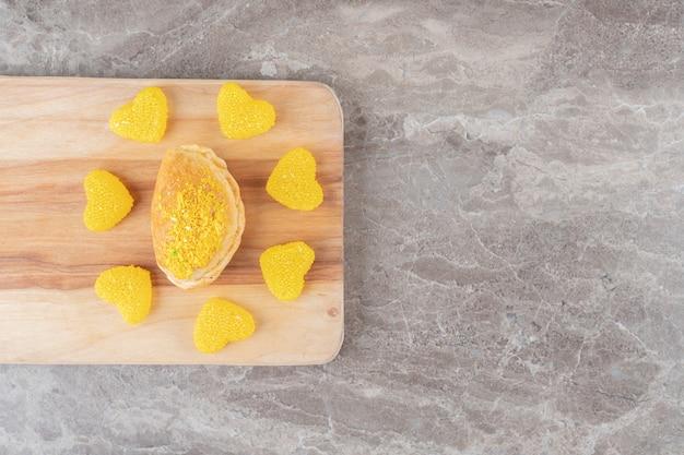 Doces de gelatina em volta de um pequeno pãozinho com cobertura em pó com sabor de limão na superfície de mármore