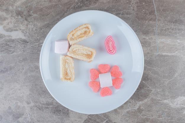 Doces de gelatina, marshmallows e rodelas de bolo em uma travessa na superfície de mármore