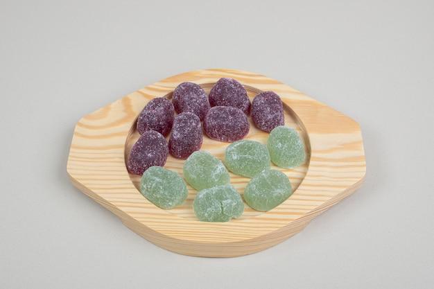 Doces de gelatina verdes e roxos em placas de madeira