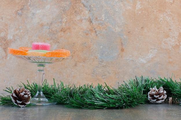 Doces de geleia de frutas açucaradas com pinhas e ramo de árvore de natal. foto de alta qualidade