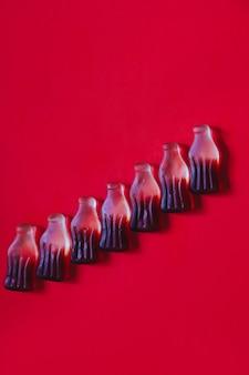 Doces de geleia de goma em fila no formato e sabor de garrafas de cola