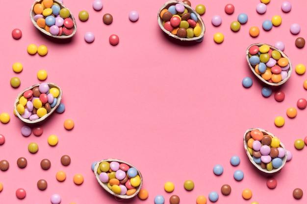 Doces de gema colorido preenchidos os ovos de páscoa quebrados no pano de fundo-de-rosa com espaço para escrever o texto no centro