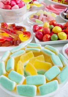 Doces de goma saborosos multicoloridos em pratos. visão vertical