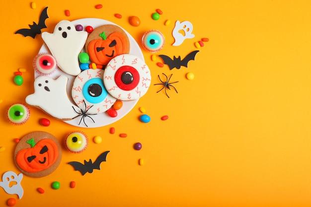 Doces de halloween em um fundo colorido close-up vista superior com lugar para texto