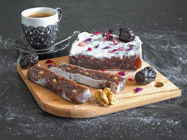 Doces de marmelada oriental com frutas de data, doces orientais em uma superfície preta.