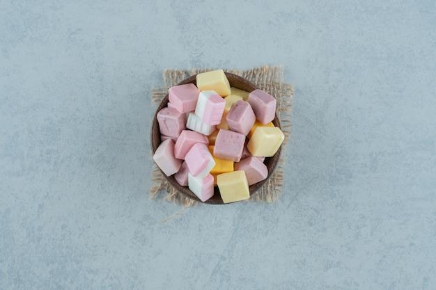 Doces de marshmallow rosa e amarelo em uma tigela de madeira na superfície branca