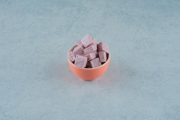 Doces de marshmallow rosa em uma tigela na superfície branca