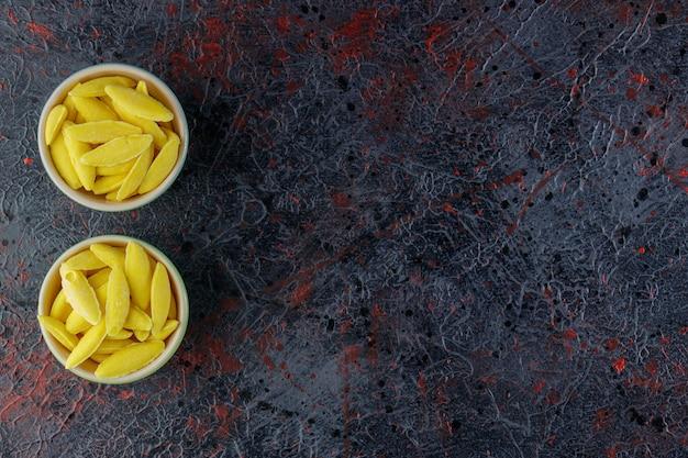 Doces de mascar em forma de banana em uma mesa escura.