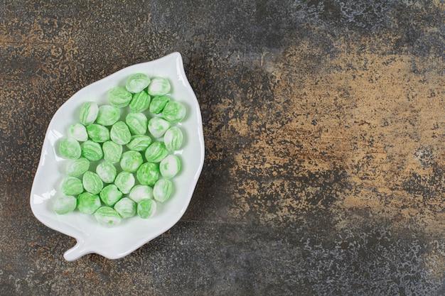 Doces de mentol verde no prato em forma de folha.