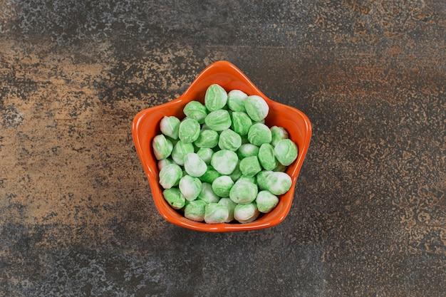 Doces de mentol verdes saborosos em uma tigela laranja.