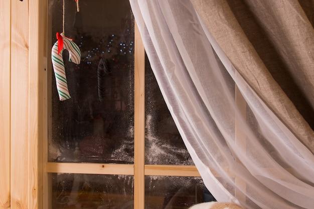 Doces de natal pendurados em uma janela rústica de madeira com geada do inverno e a cortina puxada para trás contra a escuridão do lado de fora