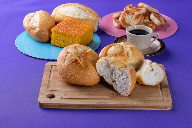 Doces de padaria em uma placa de madeira com um bolo de cenoura e pão francês ao lado de uma xícara