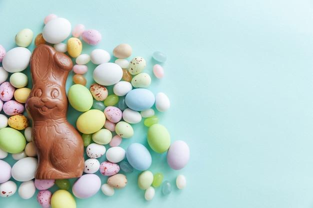 Doces de páscoa coelho ovos de chocolate e balas de geleia isoladas na mesa azul