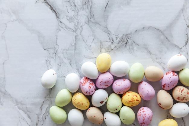 Doces de páscoa com ovos de chocolate e doces em uma mesa de mármore cinza da moda