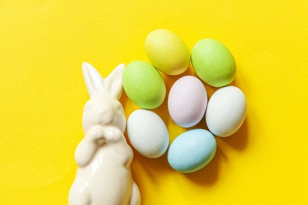 Doces de páscoa, ovos de chocolate, doces e coelho de brinquedo isolado em um fundo amarelo na moda