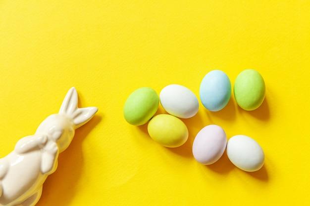 Doces de páscoa, ovos de chocolate, doces e coelho de brinquedo isolado na mesa amarela da moda