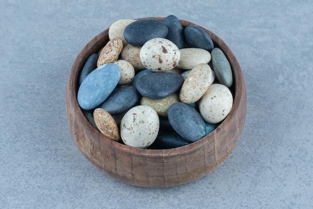 Doces de pedra do seixo em uma tigela, na mesa de mármore.