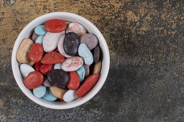 Doces de pedra em forma oval em uma tigela branca.
