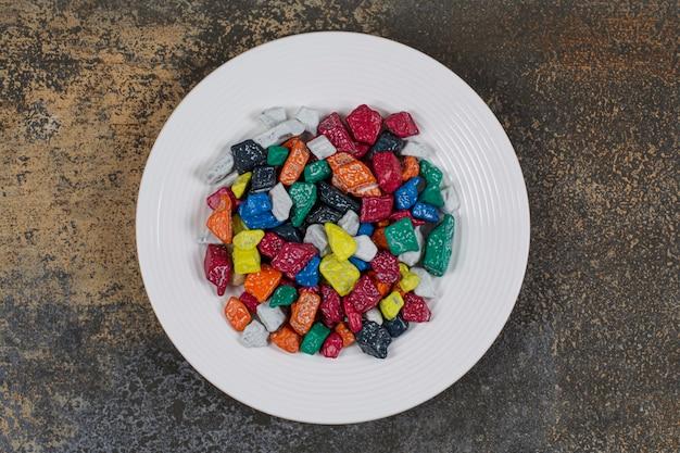 Doces de pedra multicolorida na chapa branca.