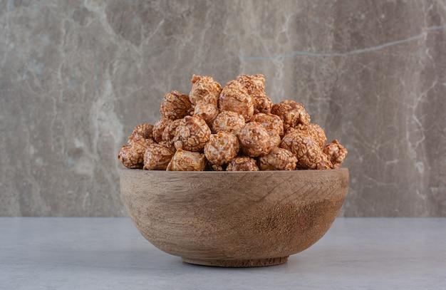 Doces de pipoca marrons empilhados em uma tigela pequena no mármore.