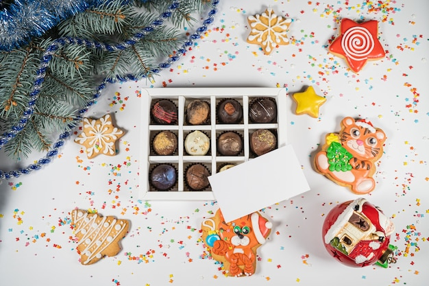 Doces de trufas de chocolate artesanais em uma caixa branca sobre um fundo de natal com cartão de visita