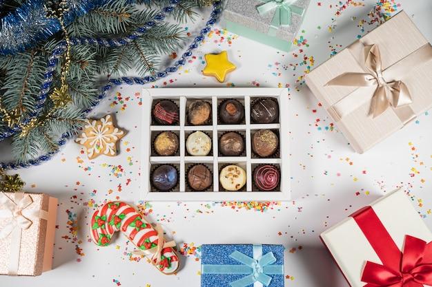 Doces de trufas de chocolate artesanais em uma caixa branca sobre um fundo de natal. diretamente acima da vista superior.