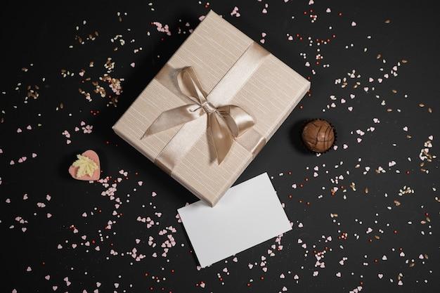 Doces de trufas de chocolate artesanais em uma caixa vermelha em um fundo escuro com cartão de visita